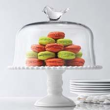 A clear glass cake dome, paired with a ceramic base, has a playful bird topper. homeessentials.com