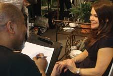 At a party hosted by Lifetime Brands, a caricaturist sketches Stefanie Stratton of Macy's.